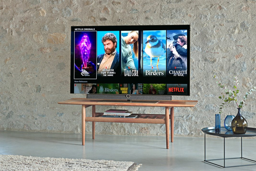 A living room with a tv on a media console with netflix on showing netflix originals