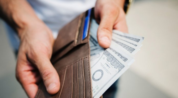 Man holding a wallet with hundred dollar bills