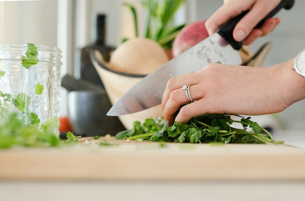 Woman's hands shown cutting up cilantro on a wooden cutting board
